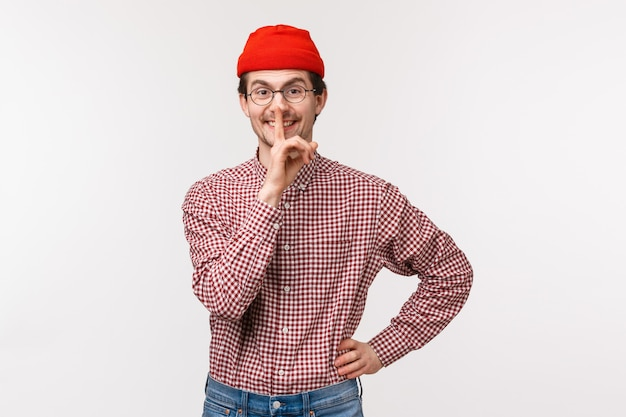 Waist-up portrait of cute happy and kind young bearded man in red beanie prepare surprise, hush at  with satisfied grin, hold index finger over lips, ask keep secret, be quiet