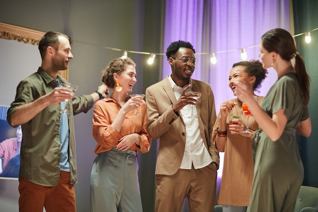 Waist up portrait of diverse group of friends having fun and drinking cocktails at home party