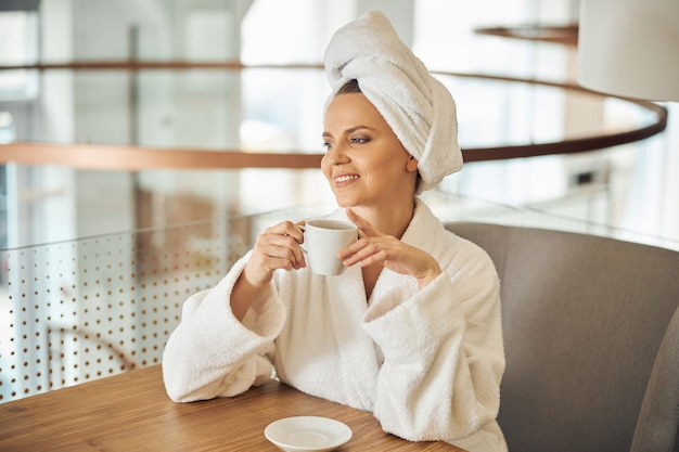 Waist-up portrait of a dreamy woman sitting at a wooden table in a wellness center