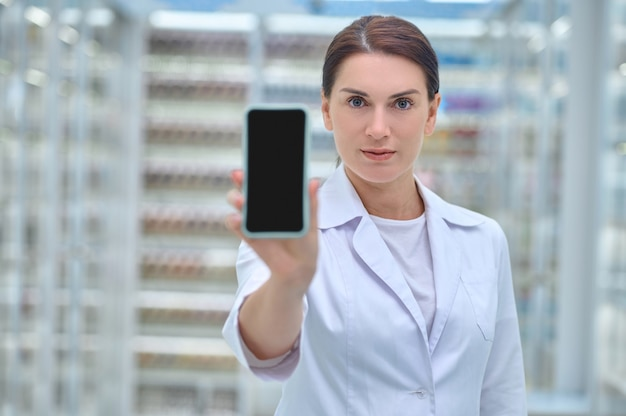 Waist-up portrait of a druggist in a clean white robe holding her smartphone in front of the camera