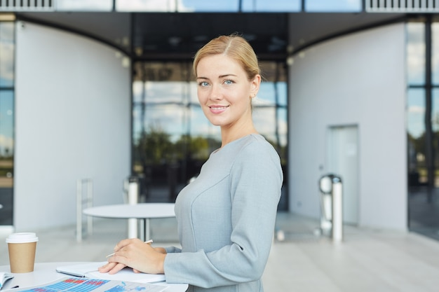 Waist up portrait of elegant blonde businesswoman smiling at camera while standing by cafe table in airport,