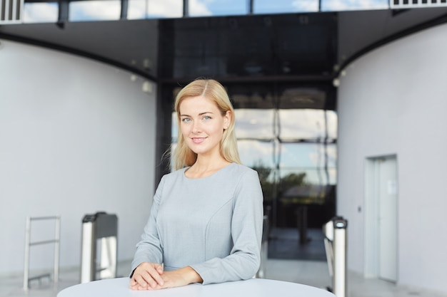 Waist up portrait of elegant blonde businesswoman  and smiling while standing at table in office building or airport,