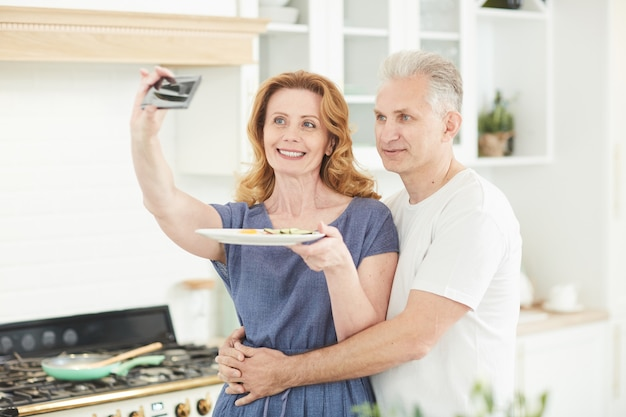 Waist up portrait of elegant mature couple taking selfie with food while cooking together in white kitchen interior at home, copy space