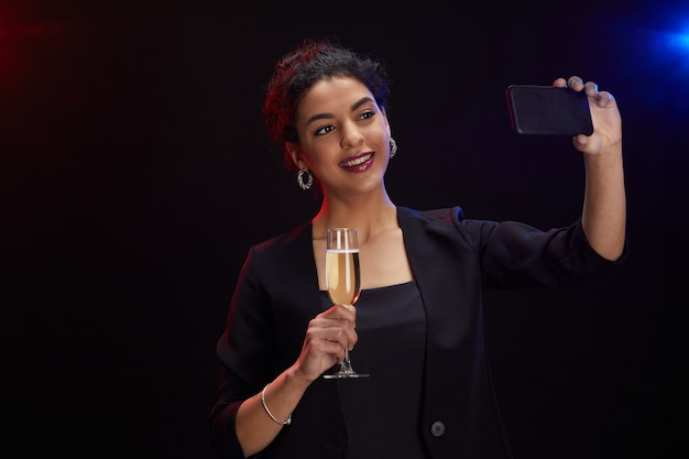Waist up portrait of elegant middle-eastern woman holding champagne glass and taking selfie photo while standing against black background at party, copy space