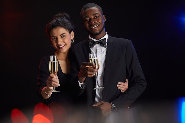 Waist up portrait of elegant mixed-race couple holding champagne glass and smiling at camera while standing against black background at party, copy space