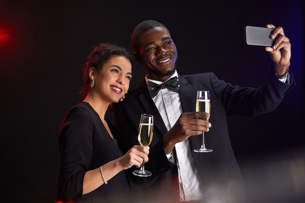 Waist up portrait of elegant mixed-race couple taking selfie photo while standing against black background at party, copy space