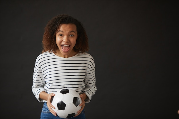 Waist up portrait of excited african-american girl holding football ball while posing