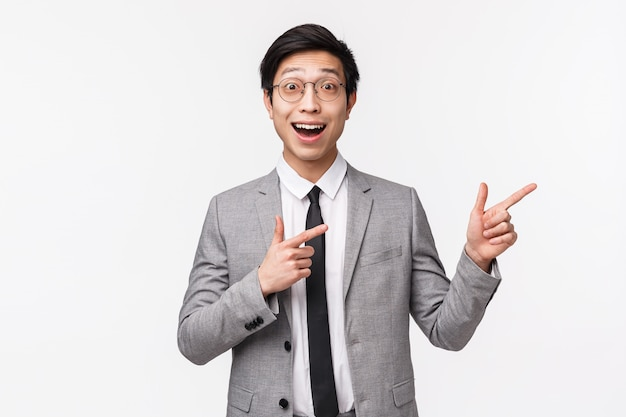 Waist-up portrait of excited and amazed, happy asian businessman in grey suit, showing you something awesome, great advertisement, promo banner on right side of copy space on white wall