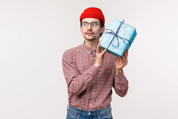 Waist-up portrait excited caucasian bearded guy in red beanie, shaking blue wrapped gift box near ear as trying guess whats inside, look thrilled, unboxing present on b-day party celebration