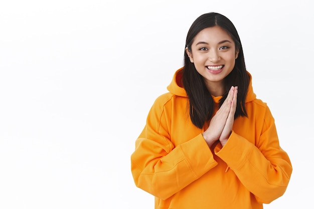 Waist-up portrait of excited cute asian girl cant wait participate in event, clasp hands, applause or rub palms as relish good outcome, smiling joyful, thanking for help, standing in plead pose