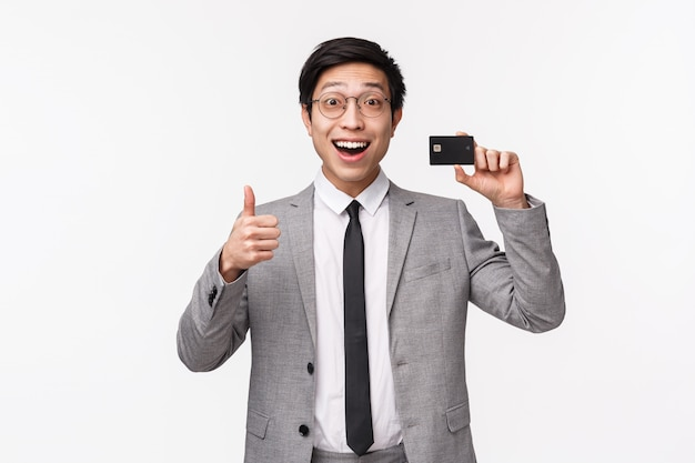 Waist-up portrait of excited, happy smiling asian male office worker, employee in grey suit and glasses, showing credit card and make thumbs-up sign, recommend bank, on a white wall