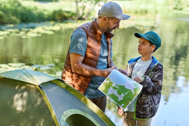 Waist up portrait of father and son looking at map while enjoying camping together by lake, copy space