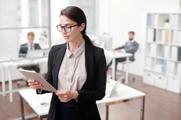 Waist up portrait of female business manager using digital tablet while standing in office, copy space