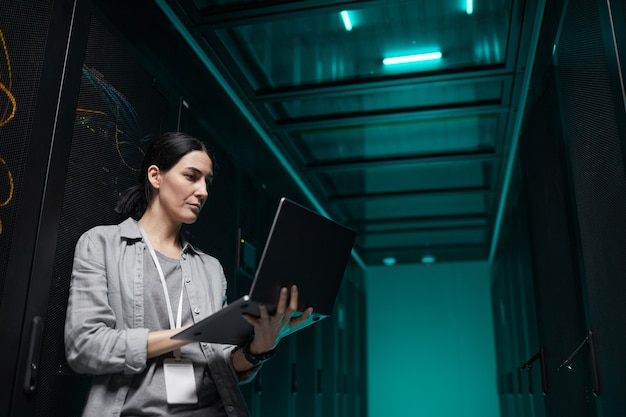 Waist up portrait of female data engineer holding laptop while working with supercomputer in server room, copy space