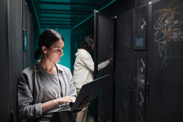 Waist up portrait of female data engineer using laptop in server room while setting up supercomputer network, copy space