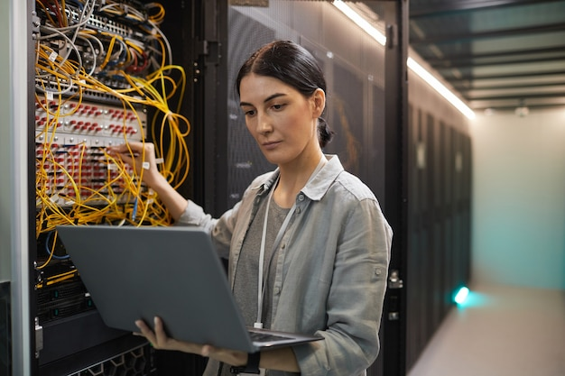 Waist up portrait of female network engineer connecting cables in server cabinet while working with supercomputer in data center, copy space
