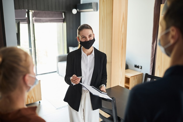 Waist up portrait of female real estate agent wearing mask while talking to young couple buying new house, copy space