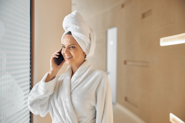 Waist-up portrait of a female with her hair wrapped in a towel talking on the smartphone