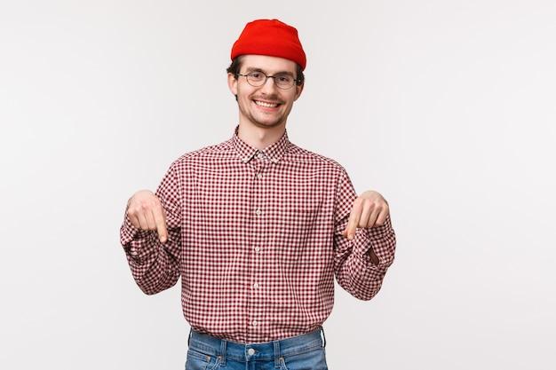 빨간 비니와 안경에 허리 위로 초상화 친화적 인 웃는 행복하고 만족스러운 젊은 남성 고객, 새로운 상점이나 응용 프로그램을 소개하기 위해 아래로 손가락을 가리키는, 배너 다운로드