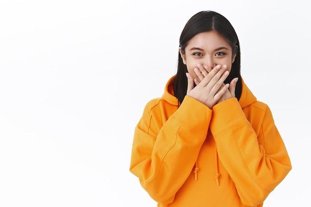 Портрет смешной и симпатичной азиатской девушки в оранжевой толстовке с завышенной талией, хихикает, пряча смех, пытается успокоиться, улыбается глазами, прижимая руки к губам, прикрывает рот ладонями, стоит белая стена