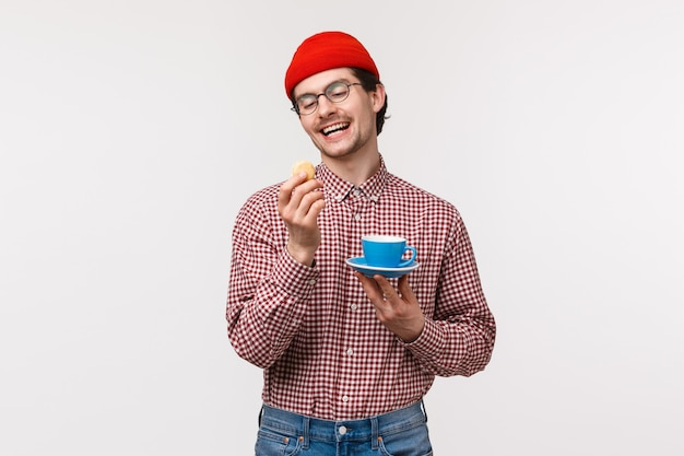 Waist-up portrait of funny caucasian hipster guy in red beanie, glasses and checked shirt, enjoying tasty cookie, eating dessert and drinking coffee or tea from blue cup on plate, on a white wall