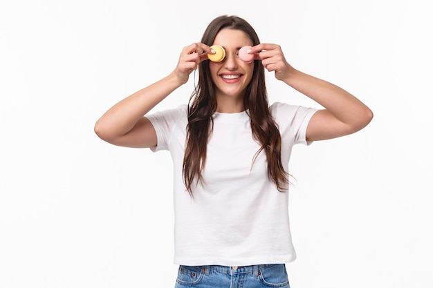Waist-up portrait of funny and cute, adorable young woman holding two desserts macarons