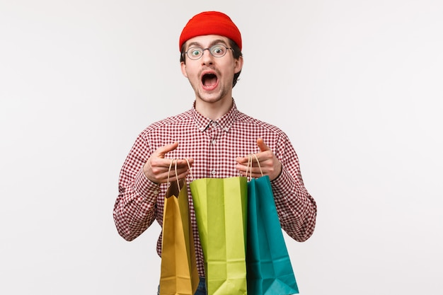 Waist-up portrait of funny and cute caucasian guy in glasses, red beanie, buy lots staff for girlfriend, hope she will like it, holding shopping bags and staring camera, wasted all paycheck in stores