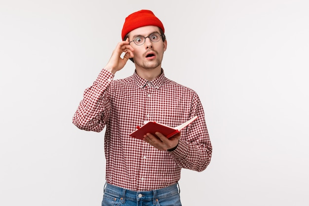 Waist-up portrait geeky and creative guy in red beanie, glasses have stunning great idea, touch temple and look inspired while taking notes in notebook, creating equation, stand on a white wall