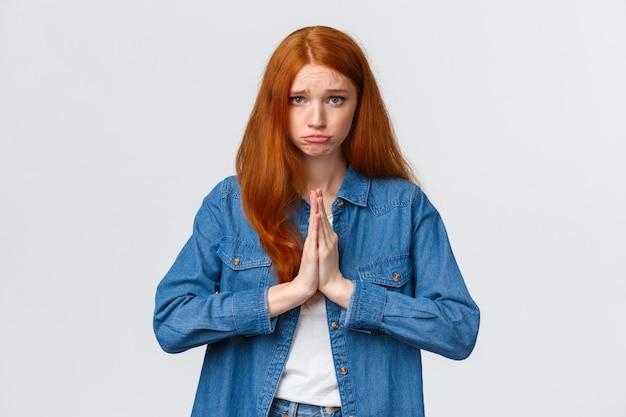 Портрет талии, мрачная милая рыжая девушка, просящая извинения, сжимает руки в молитве, надуться и смотрит в камеру, умоляя, прося помощи, извините, чувствуя сожаление из-за того, что стала причиной беспорядка,