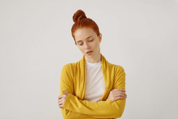 Waist up portrait of gorgeous young caucasian woman with delicate features and ginger hair looking down with sad unhappy expression with arms crossed