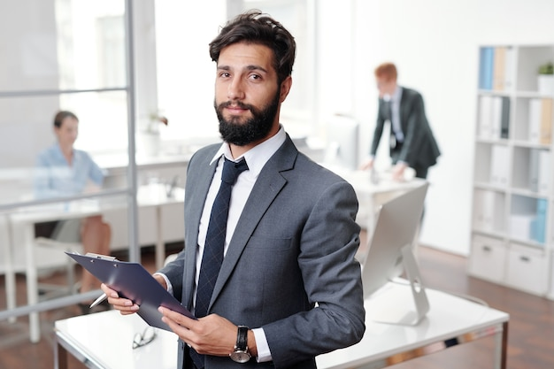 Waist up portrait of handsome bearded businessman and holding clipboard while posing in office, copy space
