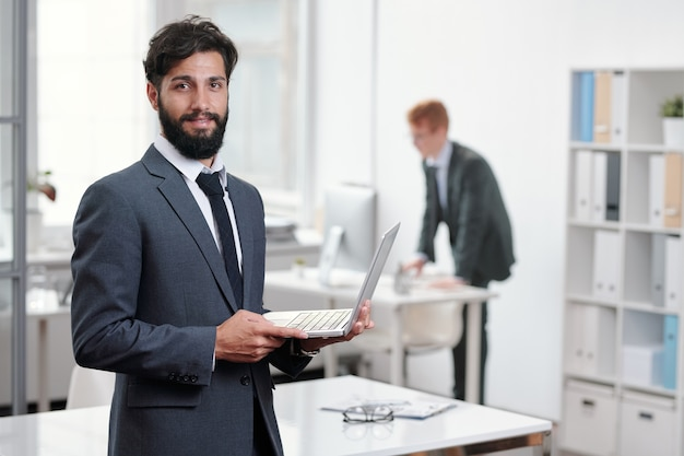 Waist up portrait of handsome bearded businessman and holding laptop while posing in office, copy space