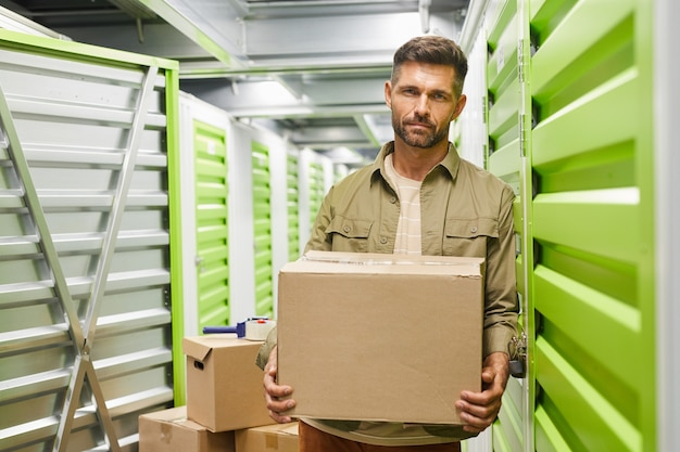 Waist up portrait of handsome bearded man carrying cardboard box  while standing in self storage facility, copy space