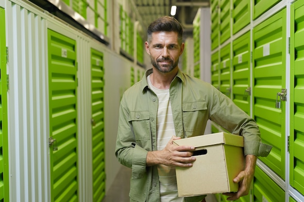 Waist up portrait of handsome man holding cardboard box standing in self storage facility and , copy space