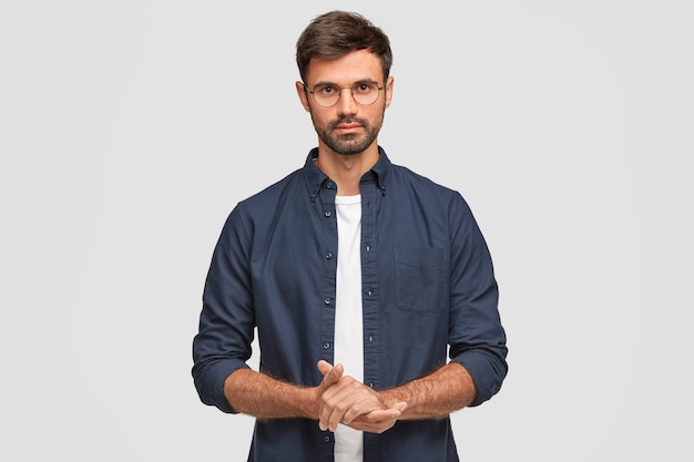Waist up portrait of handsome serious unshaven male keeps hands together, dressed in dark blue shirt, has talk with interlocutor, stands against white wall. self confident man freelancer