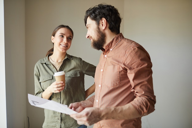 Waist up portrait of happy couple looking at color floor plans while redecorating house, copy space