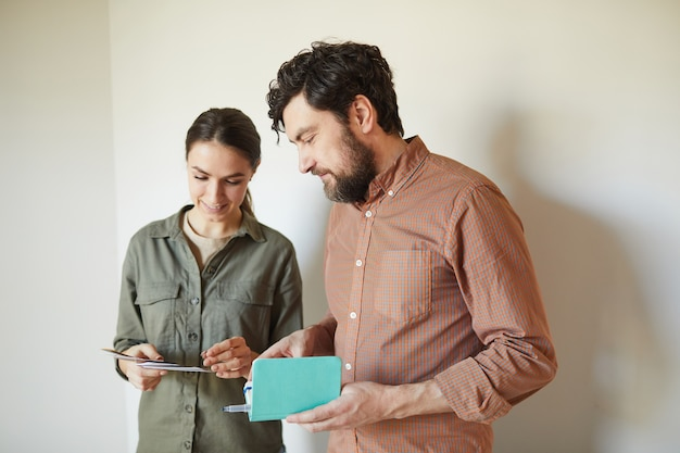 Waist up portrait of happy couple looking at color samples standing by white blank wall while redecorating house, copy space