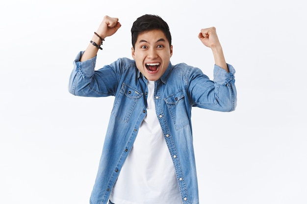 Waist-up portrait of happy, excited young smiling man shouting hooray or yes, raising hands up, fist pump in joy, rejoicing over win, achieve goal, celebrate victory or success, white wall