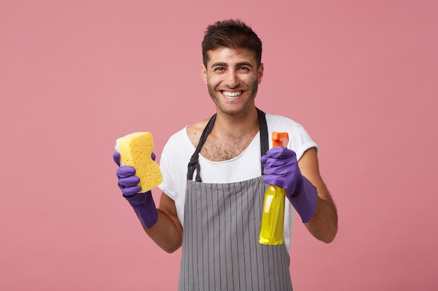 Waist-up portrait of happy positive young man with beard smiling broadly while doing housework by himself, wearing apron and protective rubber gloves, holding cleaning spray and yellow sponge