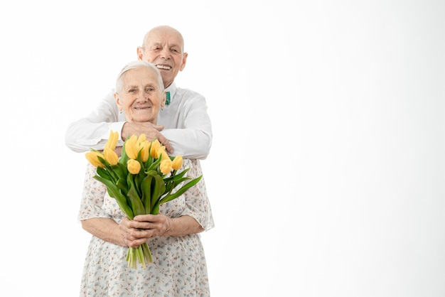 Waist up portrait of the happy smiling old couple with a bouquet