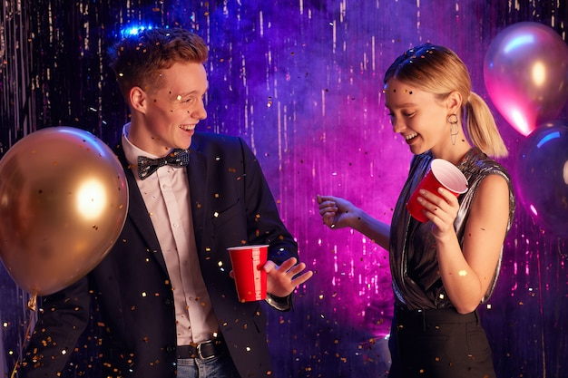 Waist up portrait of happy teenage couple dancing in decorated hall and holding red cups while enjoying prom night or party