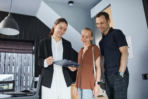 Waist up portrait of happy young couple talking to real estate agent while buying new house, copy space