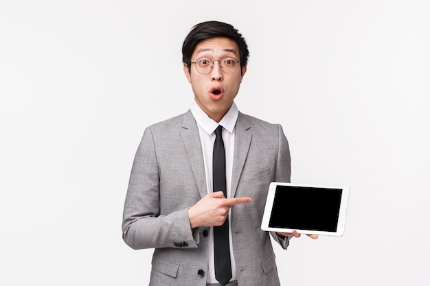 Waist-up portrait of impressed, curious asian young man in grey suit and glasses, asking question about something he saw in internet, pointing at digital tablet screen, look  intrigued