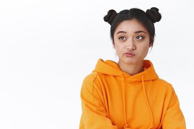 Портрет с приподнятой талией, нерешительная милая азиатская девушка, которая думает о чем-то, стоя у белой стены, с ухмылкой смотрит влево, сомневается и неуверенно, обдумывает трудное решение