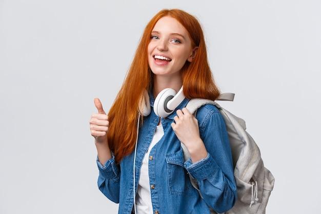 Портрет талии радостная милая рыжая девушка, приглашающая первокурсников подать заявку на обучение, получила стипендию, улыбаясь, показывая вверх большие пальцы в знак одобрения