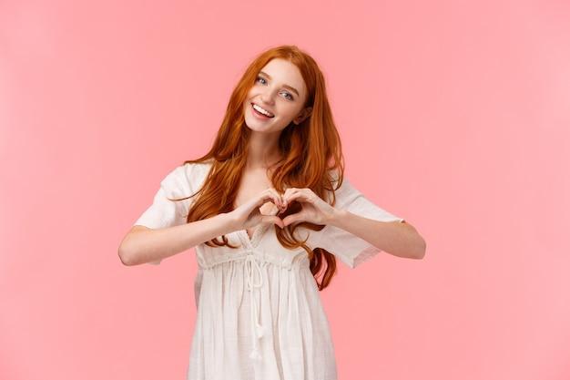 Талия-up портрет прекрасной, романтичной и милой европейской женщины с рыжими волосами, наклонив голову и улыбаясь, говоря, люблю тебя, сделай сердечный жест как, выразить привязанность или сочувствие, счастливый день святого валентина