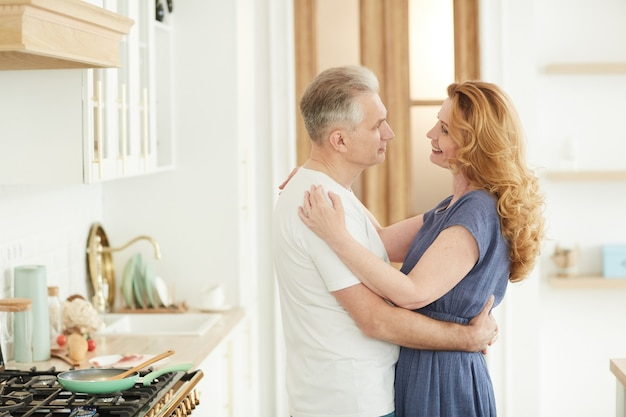 Waist up portrait of loving mature couple embracing and looking at each other while standing in white kitchen interior at home, copy space