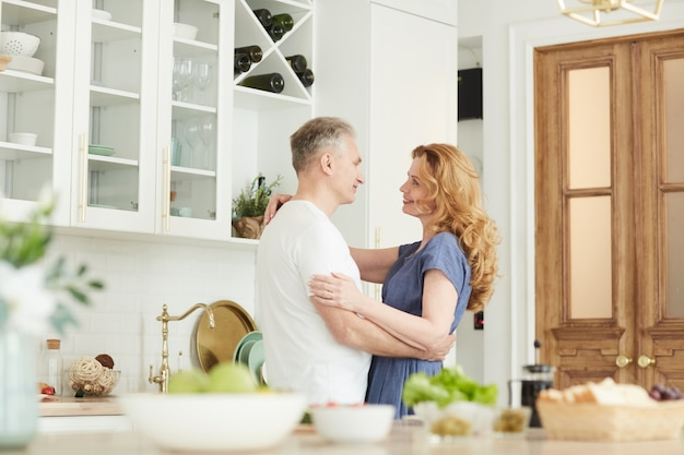 Waist up portrait of loving mature couple embracing and looking at each other in white kitchen interior at home, copy space