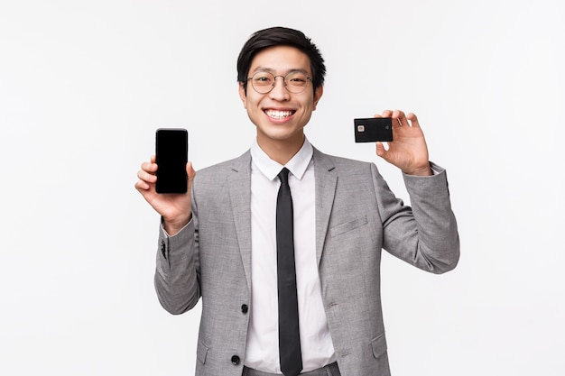 Waist-up portrait of lucky, good-looking asian businessman in grey suit, glasses showing mobile phone display and credit card, smiling pleased, advice download banking app, use non-cash payment