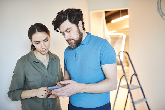 Waist up portrait of married couple using smartphone for design ideas while renovating house together, copy space